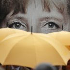 Supporters of the Christian Democratic Union (CDU) hold umbrellas in front of a giant portrait of German Chancellor Angela Merkel.<span class=