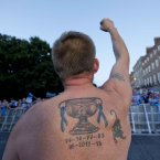 Robbie Henry from Coolock shows off his new tattoo to the crowd<span class=