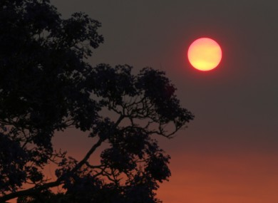 The sun glows a deep orange colour as the light is filtered through smoke haze from wildfires drifts over Sydney.