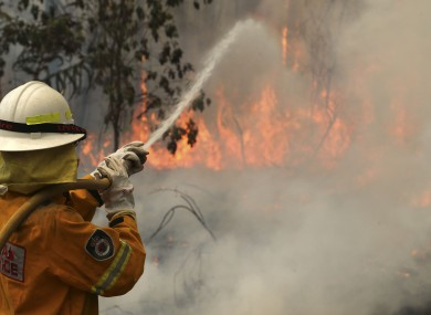 A firefighter tries to control flames near houses at Bilpin, 75 kilometres west of Sydney