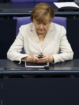 German Chancellor Angela Merkel uses her mobile phone.