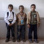 Syrian children pose for a portrait in their classroom.<span class=