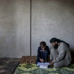 Ahmed al-Fikri helps his 12-year-old son Abdo al-Fikri with his homework at their family house in Madaya village<span class=