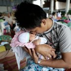An refugee from Typhoon Haiyan cuddles his new born baby daughter.<span class=