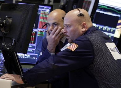 A pair of traders work in their booth on the floor of the New York Stock Exchange earlier
