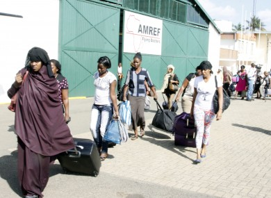 Kenyans carry their bags after being evacuated from South Sudan by the Kenyan Defence Forces at Wilson Airport in Nairobi, Kenya.