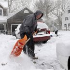 Craig and Barbara Clasen use shovels to dig their driveway out in Shoreham, NY<span class=