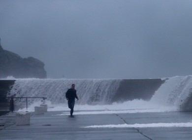A man runs from waves crashing onto the East pier in Howth yesterday