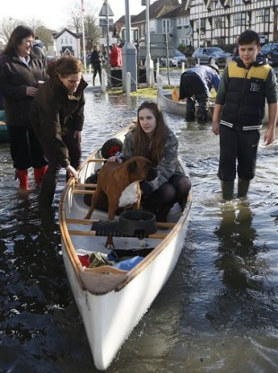 A girl sits with her dog in a boat on a flooded street, in Datchet, England.