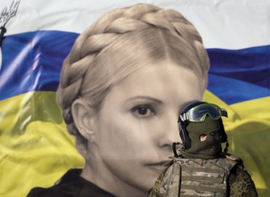 A uniformed anti-government activist walks past a poster depicting jailed former Ukrainian premier Yulia Tymoshenko.
