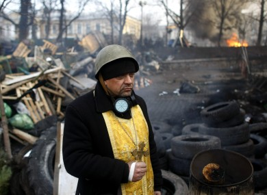 A priest stands on the barricades at Independence Square this morning.