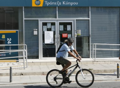 A man passes with a bicycle outside from a branch of Bank of Cyprus in Nicosia