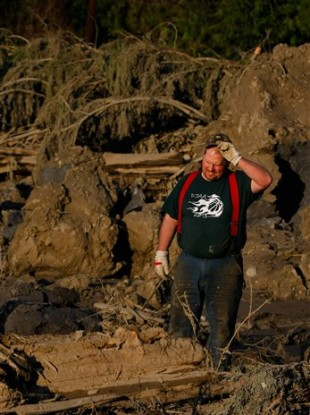 Jason Anderson searches through rubble for bodies.
