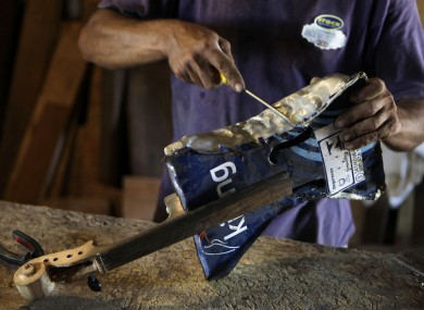Nicolas Gomez makes a violin with recycled materials at his home in the Cateura.
