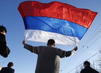 An activist carries a Russian flag during a rally at a central square in Donetsk, eastern Ukraine