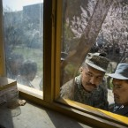 An Afghan soldier, left, and a police man peek through a window as they queue with others to get their registration card.<span class=
