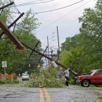 Residents survey damage along a street.<span class=
