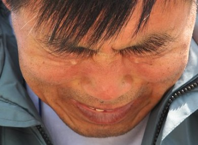 A relative of a passenger aboard the sunken ferry Sewol weeps as he waits for news on his missing loved one at a port in Jindo, South Korea.