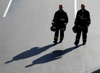 A pair of firefighters arrive at the finish line of the Boston Marathon.