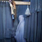 An Afghan woman waits in a changing room to try out a new Burqa.<span class=