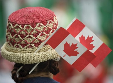 A woman wears miniature Canadian flags as she celebrates Canada Day.