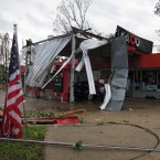 An American flag stands limp in front of a gas station-convenience store that had its roof mangled by a tornado.<span class=