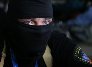 A masked pro-Russian activist guards looks through a window of the regional administration building seized  in Donetsk.
