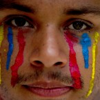 A university student wearing painted tears in the colors of Venezuela's flag looks into the camera during an anti-government protest in Caracas, Venezuela (AP Photo/Fernando Llano).<span class=
