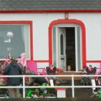 A small dog watches the riders pass along the Antrim coast.<span class=