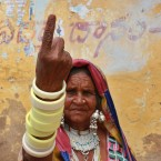 An Indian tribal woman displays the indelible ink mark on her finger after casting her vote at a polling station on the outskirts of Hyderabad, India. Millions of people in nine states across India, including the newest state of Telangana, were voting Wednesday in the latest phase of the country's massive general election. <span class=