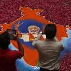 Indians take photographs of a portrait of Bharatiya Janata Party (BJP) leader Narendra Modi, made with colored powder and surrounded by rose petals, at the party office in Gandhinagar, in the western Indian state of Gujarat.<span class=