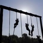 Freshman midshipmen, known as plebes, climb ropes on an obstacle course during Sea Trials, a day of physical and mental challenges that caps off the freshman year at the US Naval Academy in Annapolis, Maryland. <span class=