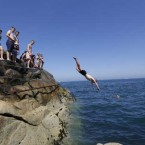 Young people jumping into the sea of the side of a ledge along the coast of Dun Laoghaire. During the hottest week of the year so far. <span class=