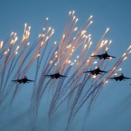 Belarusian army jet fighters fly and launch flares during a parade marking Independence Day in Minsk, Belarus.<span class=