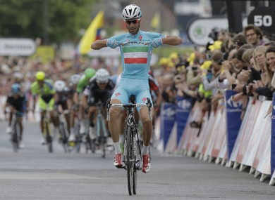 Vincenzo Nibali points to his shirt as he crosses the finish line ahead of the sprinting pack to win the second stage.