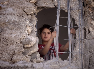 Child looks out from the damaged family home of Palestinian Ziad Awad in the town of Idna,13 kilometers west of the West Bank city of Hebron.