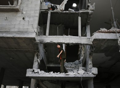 A Palestinian looks at the damage to a house following an overnight Israeli missile strike in Gaza City.