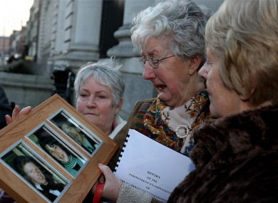 Bride McDermot (centre) holds a picture of her children George,Marcella and William