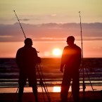 Fishermen make the most of the daylight as they cast into the sea at Woolacombe beach, North Devon, as the sun sets after another hot day in the South West UK.<span class=