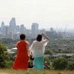 Visitors enjoying a view of the City of London from Parliament Hill in Hampstead Heath, London, during a spell of hot weather.<span class=