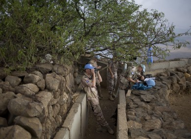 U.N. peacekeepers from the United Nations Disengagement Observer Force, also known as UNDOF, observe Syria's Quneitra province at an observation point on Mt. Bental in the Israeli-controlled Golan Heights.