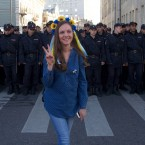 A woman wearing traditional Ukrainian flower headband poses for a photo in front of police officers, during an anti-war rally in downtown Moscow, Russia.<span class=