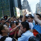 A local policeman scuffles with residents and pro-Beijing supporters as they try to attack a student pro-democracy activist.<span class=