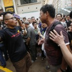 A pro-democracy student protester argues with angry locals.<span class=