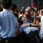 A local policeman falls during one of the confrontations.<span class=