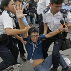 A pro-democracy protester is taken away by police officers.<span class=