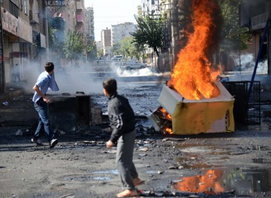 Teenagers set on fire barricades despite a curfew as Turkish army tanks station in Diyarbakir hours after violent protests between Kurdish protesters and Turkish police.