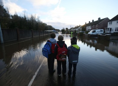 Children look at flood water on Nutgrove Avenue in Dublin on their way to school on Friday.