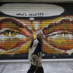 A man passes a closed apparel shop with a graffiti on the shutter in Athens during the mid-season sales.<span class=