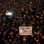 People gather to pay their respects for the victims of a terror attack against a satirical newspaper in Paris. Masked gunmen shouting